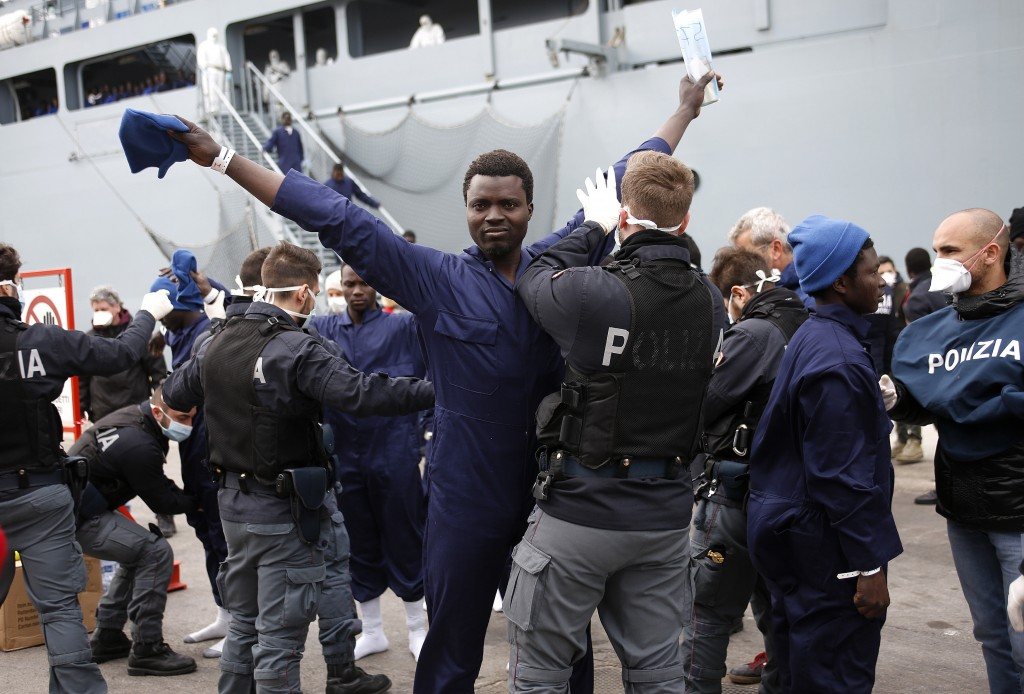 Migrants are inspected by policemen as they disembark the German naval vessel Frankfurt Am Main in the Sicilian harbour of Pozzallo