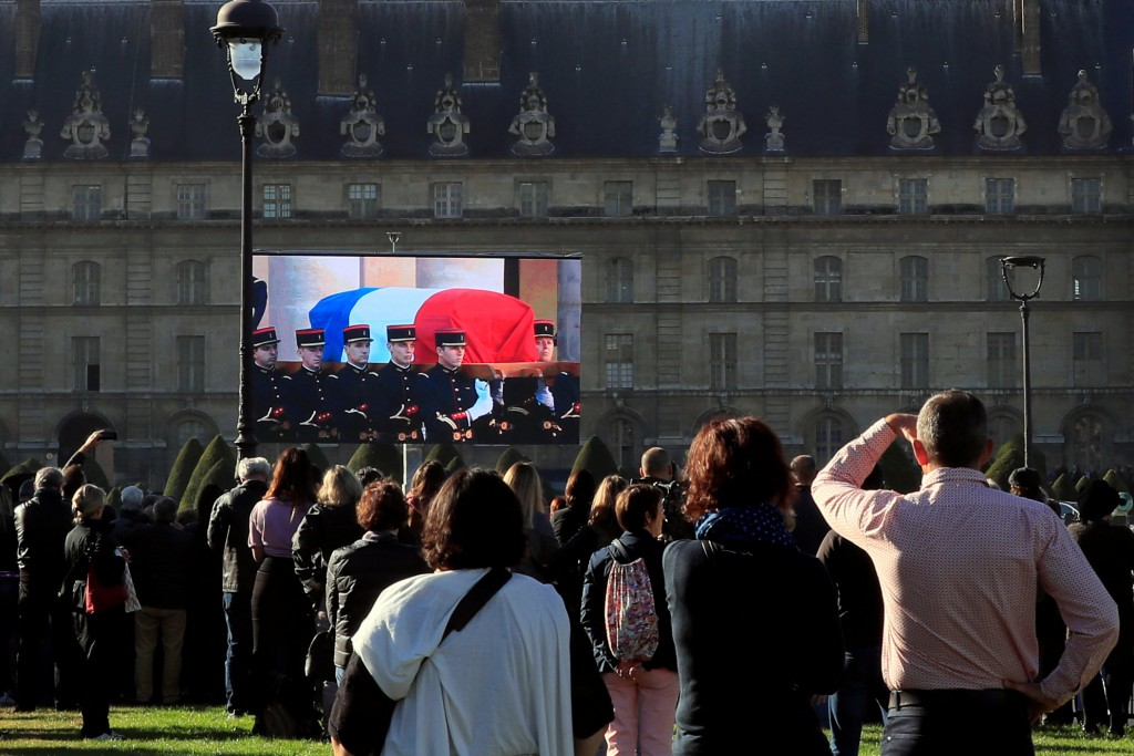 People watch a giant screen during a national tribute for late singer Charles Aznavour at the Hotel des Invalides in Paris